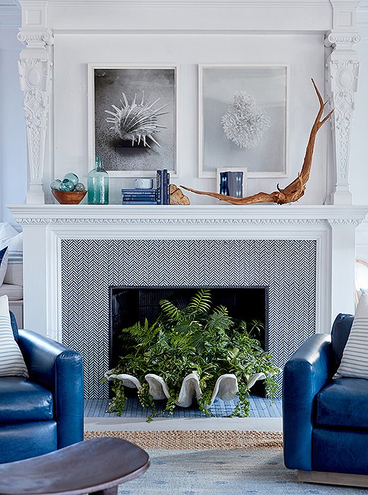 Two framed photographs by Dawn Wolfe crown the space's grand mantel, accented with organic objects and sea-blue glass.