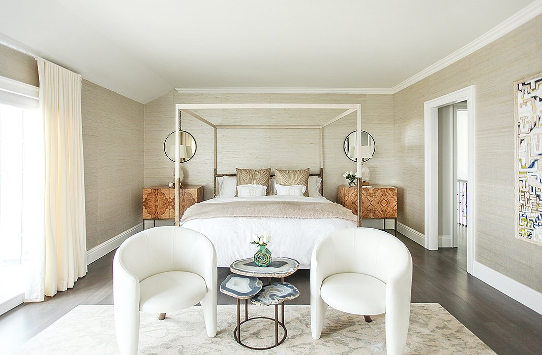 Upstairs, the master bedroom's neutral palette, similar to that of a birch tree, creates a calm space perfect for rest and relaxation. On the walls, raffia wallpaper from Ralph Lauren adds texture and depth without detracting from the room's statement pieces.