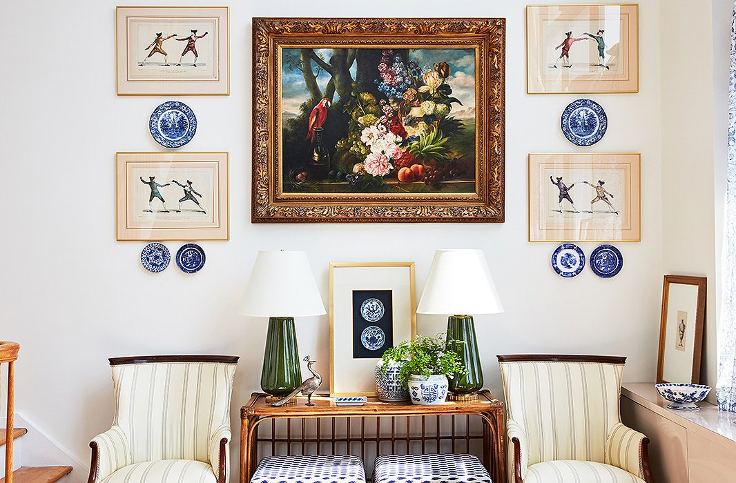 The team from One Kings Lane Interior Design helped Stephanie create the perfect gallery wall by flanking a large painting with framed prints and delft plates. A pair of ceramic lamps by Bunny Williams Home plays up the symmetry.