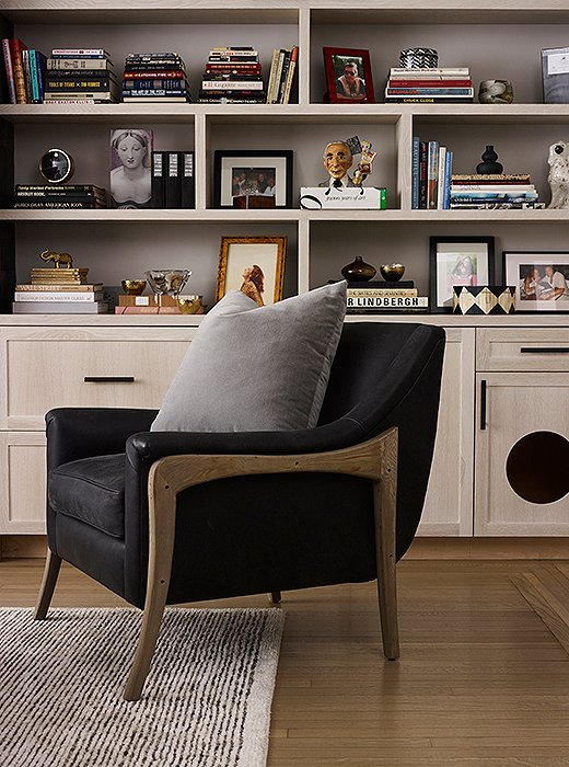 In the living room, a leather armchair by Brownstone features wood accents selected to complement the sofa, cabinetry, and floors. Behind, artfully arranged bookcases showcase Morgan and Suki's extensive collection of coffee table books, photographs, and objets.