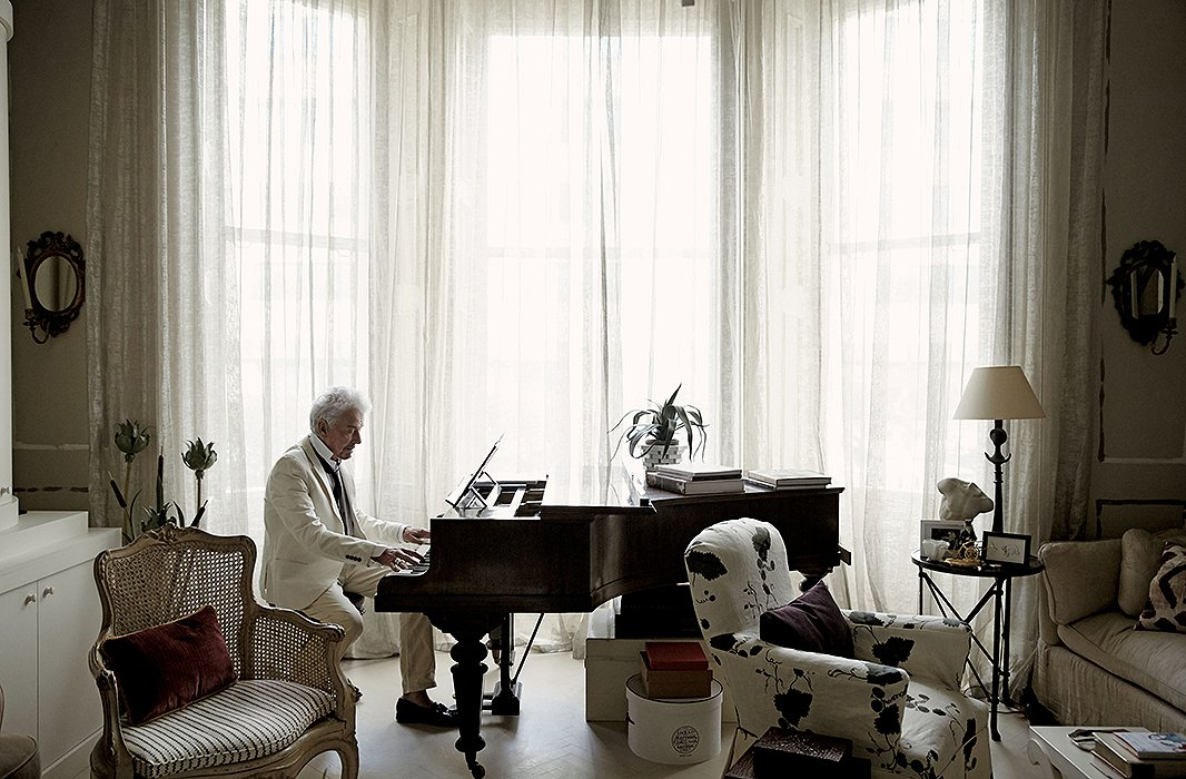 Healthy distractions: Designer Nicky Haslam at home with his Steinway.