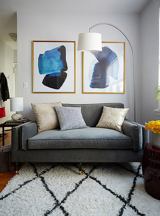 A Moroccan rug along with a streamlined arching floor lamp and graphic art help anchor the living area as a distinct space.