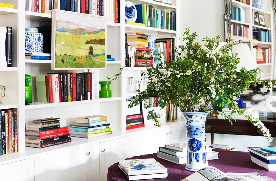Built-in bookshelves in CeCe's Manhattan apartment hold her treasured design library, along with a mix of modern blue-and-white plates, green Italian art glass, and traditional chinoiserie ceramics.