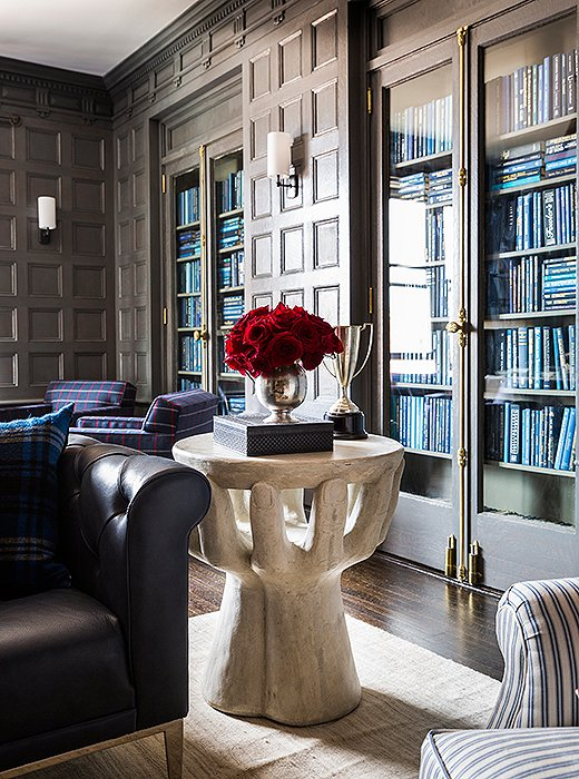 A sculptural resin side table adds height and heft beside a chesterfield sofa. On top, vintage trophies in pewter and silver lend the striking vignette a classic twist.