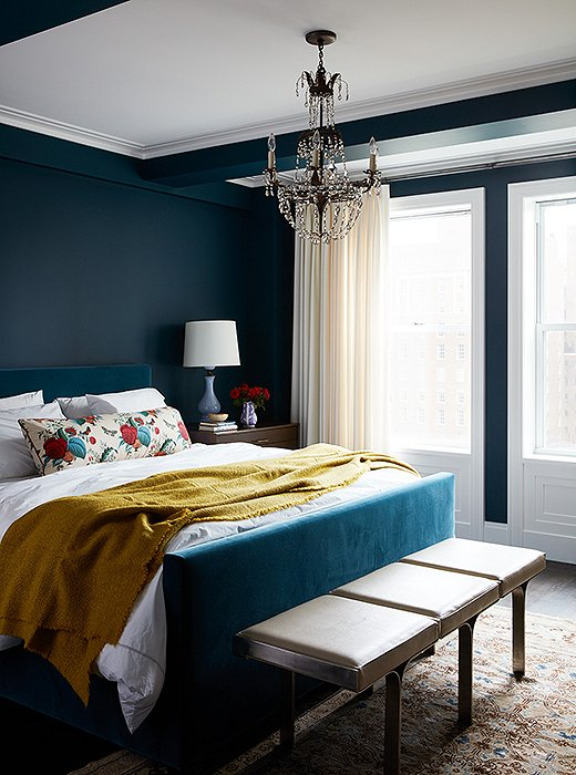 A velvet-upholstered bed blends seamlessly with the peacock-blue walls in the master bedroom.