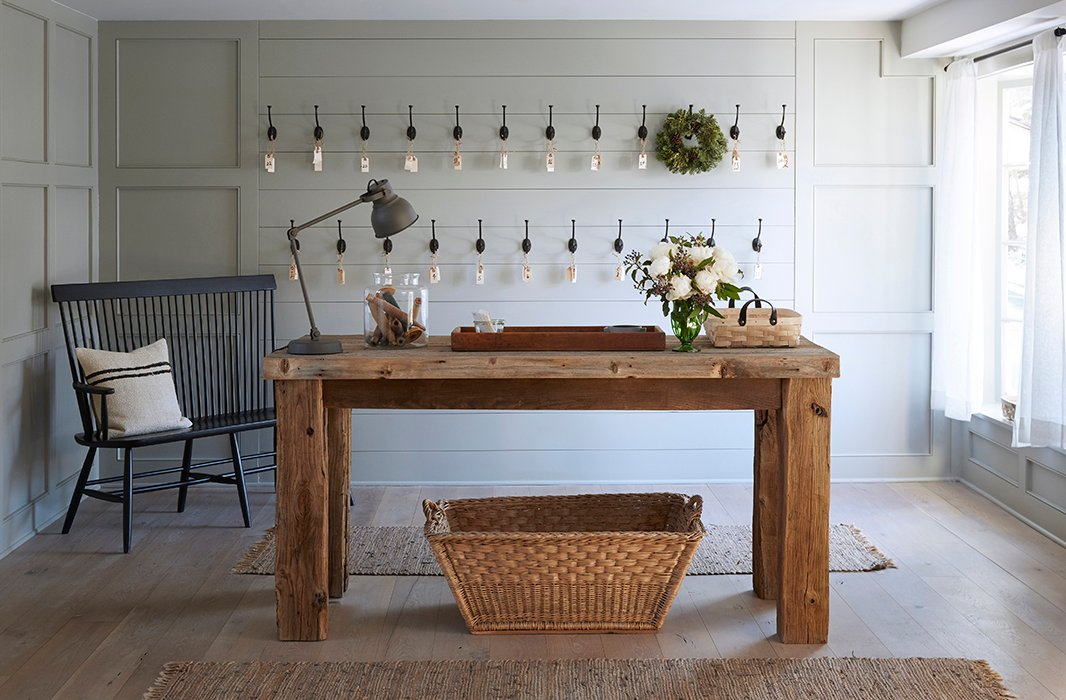 A farm table custom-made by local craftsmen acts as a welcome station. Behind, shiplap walls and a Windsor bench exemplify country chic.