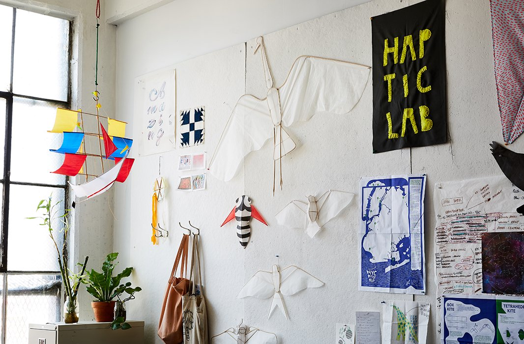 A few of Haptic Lab's popular kites, fashioned in the shapes of sailing ships and animals, hang alongside patterned fabric swatches and printed maps in the studio.