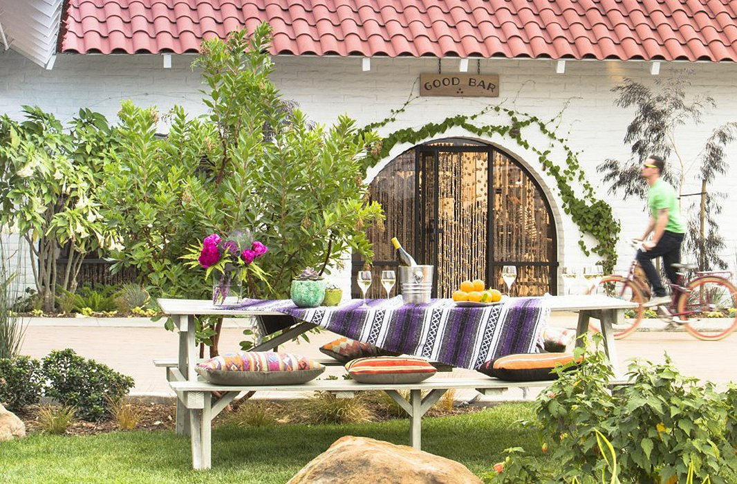 Make a picnic table a little more comfy with a pile of plush textiles. Photo courtesy of The Goodland.
