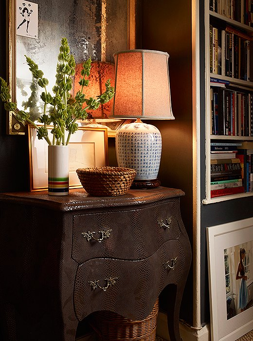A bombé chest finished in faux lizard serves as a snazzy foundation to an otherwise traditional vignette. Details such as a nubby Empire lampshade and a woven basket turned catchall epitomize Michael's penchant for rusticity.