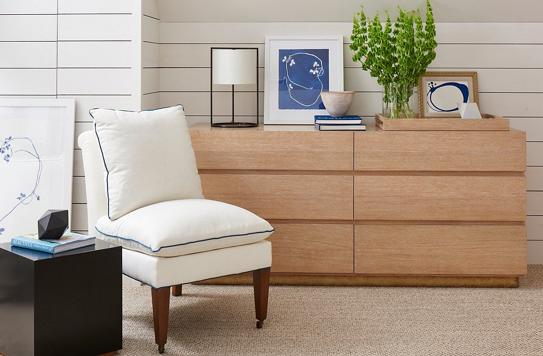 The cerused-oak Santa Monica Dresser and linen-upholstered Loring Slipper Chair, both by Mark D. Sikes for Henredon.