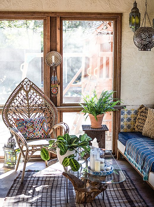 Moroccan-inspired lighting, a vintage tree-trunk table, a rattan chair, and a host of vintage textiles make for a delightfully laid-back sitting area. Photo by Shayna Fontana.