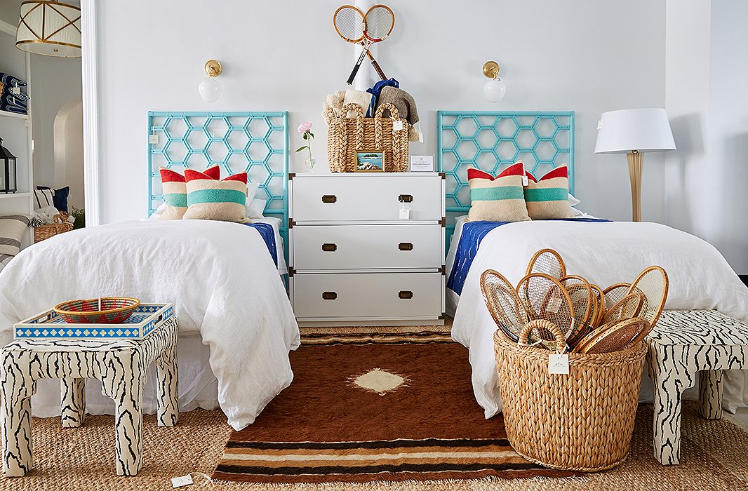 Twin beds, a campaign chest, and rattan headboards result in a practical arrangement for two. A basket of vintage rackets lends an expected vignette a bit of fun.