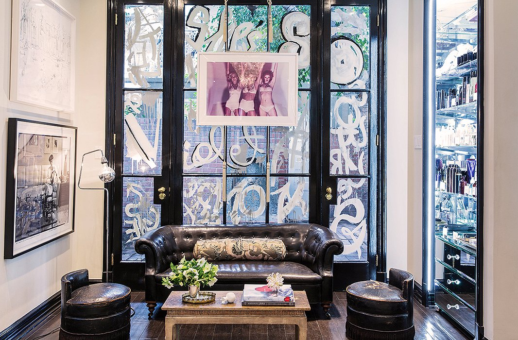 Cassandra and Bill Sofield had the idea to graffiti the lounge area windows in French script, which was painted by John Opella. The print hanging in front is by Guy Bourdin, and the photograph and the sketch are by Edith Head.