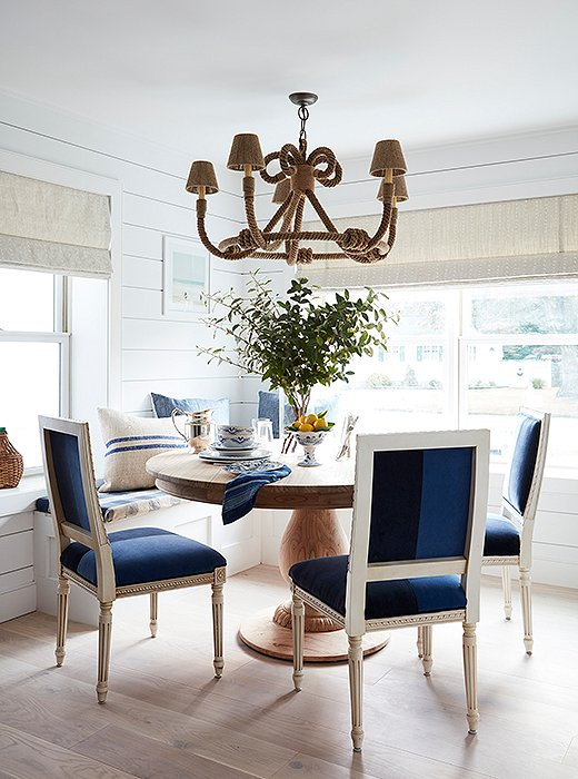 "Toby and Will had a banquette installed during the renovation, a decision they feel ""encourages guests to linger."" Beneath a rope-wrapped chandelier by Jamie Young, a round pedestal table and color-blocked velvet chairs provide just the right amount of comfort and formality."