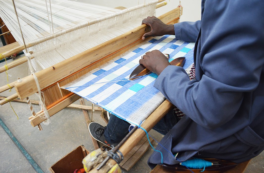 One of Bolé Road's artisans in Ethiopia weaves together fibers to create fabric for a pillow. Photo courtesy of Bolé Road.