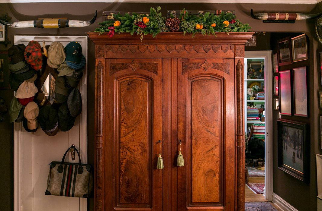 """One of my favorite things to do at the holidays is bring the outside inside,"" Bob writes. Atop an antique armoire, a garland of evergreen branches, pinecones, and citrus forms an organic counterpoint to all the vintage glitz and glimmer."