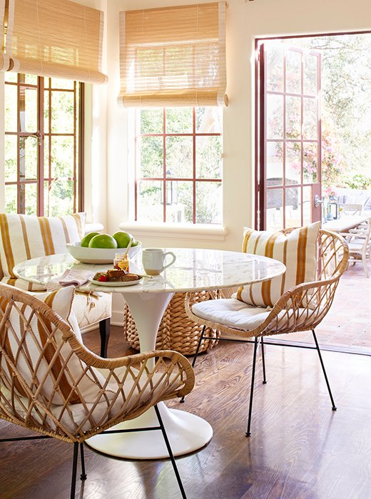 A touch of midcentury, courtesy of the marble-top Tulip table and rattan chairs, brings a sophisticated sense of boho style into the mix.