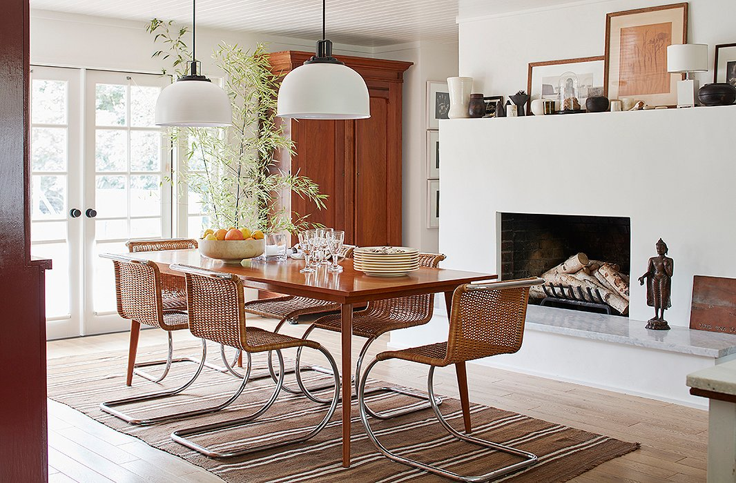 "Chairs by Mies van der Rohe surround a midcentury table. ""I think my favorite spot in the house is the dining room,"" says Laura. ""It has a beautiful view of the garden, which lends it a meditative quality."" French doors installed by Cloud allow for plenty of light—a far cry from the dim space it once was."