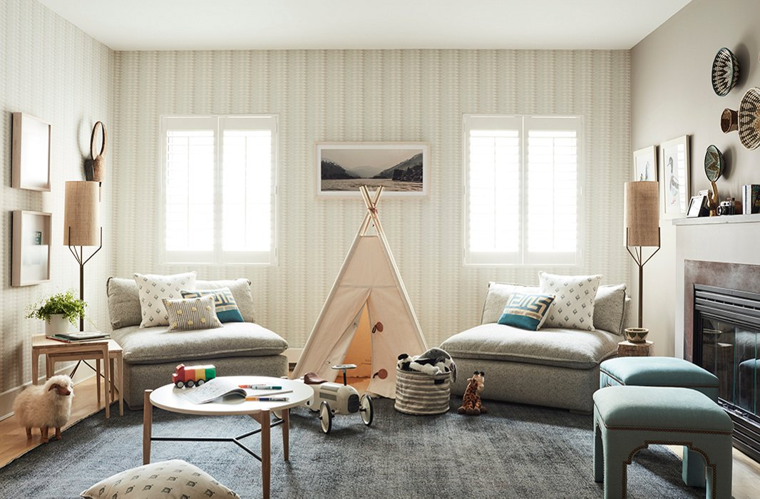 A tepee between windows encourages imaginative moments of play, while a low-lying table offers a surface for crafts and games. What appear as two oversize chairs serve double duty as a sofa; they can easily be pushed back together when the tepee is not in use.