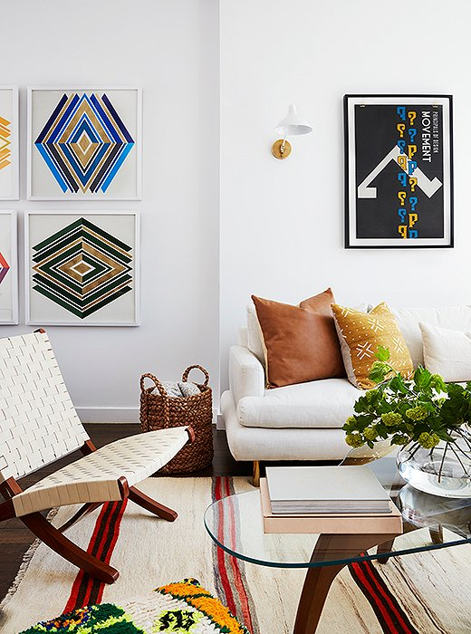 It's on the left side of this wall where we discover Mindy's penchant for bling. Custom graphic prints by Wonderwall feature the space's token touches of blue and green, atop which layers of gold leaf shine. Above the sofa, sconces by AERIN flank another punchy piece.