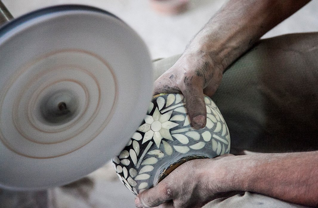 An artisan smooths the surface of a bone-inlay bowl. Photo courtesy of Mela Artisans.
