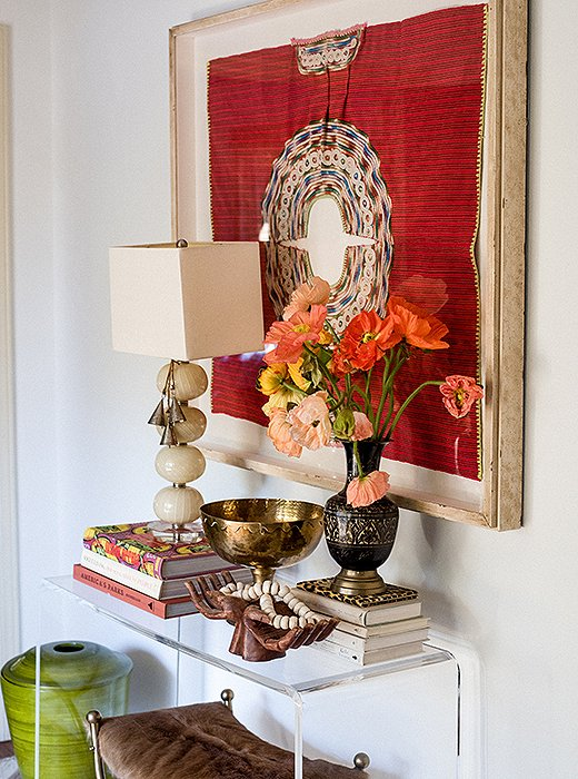 A woven huipil Paula found on a trip to Mexico was framed and hung above an acrylic console.