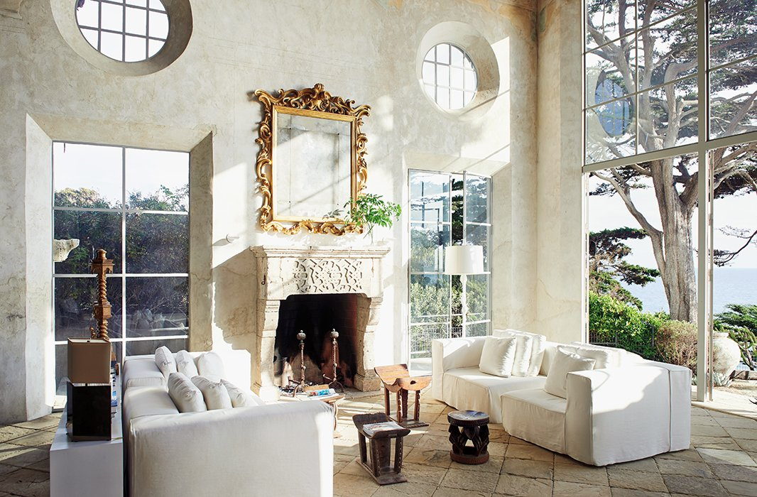 Plaster walls and rustic stone floors are offset with white upholstery at Richard's Marrakech-inspired house.