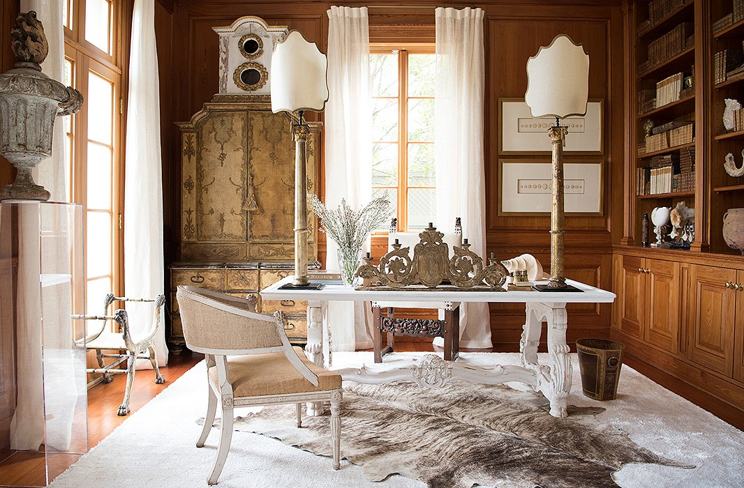 "With Italian Corinthian fragments (made into desk lamps) and a reliquary standing atop a secretary, Tara's office hits a high note of European grandeur—as she puts it, ""When you walk into the room, you see this beautiful Old World visual."" She saves it from feeling heavy by sprinkling in neutrals. Opposite this Old World visual are the 21st-century technologies that make the office tick."