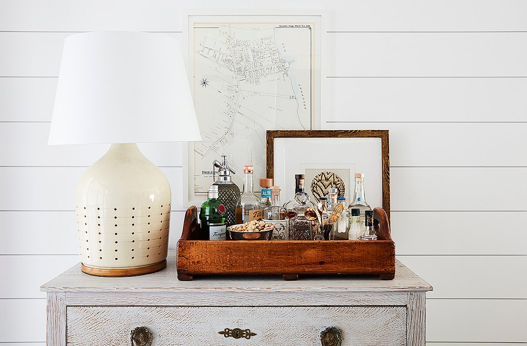 "A Ralph Lauren Home lamp sits atop a vintage chest with an oversize tray transformed into a bar. ""It's a move that allows you to take the party wherever it needs to be,"" Sally says, and encourages guests to help themselves while you're busy hosting. A map, picked up by Will on his travels, hangs on the wall behind."