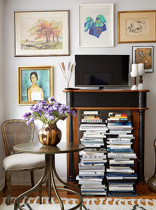 A vintage bistro table serves as Ari's worktable, dinner surface, and bar when hosting friends; Anthony brought in an ornate wood mantel that elevates the TV while holding Ari's books.