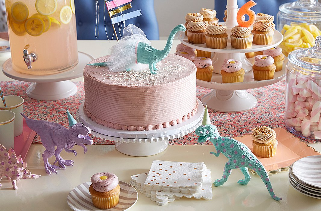 A pretty tablescape comes together quickly with ceramic cake stands and glass jars, which instantly elevate store-bought confections. Toy dinosaurs painted in pastel hues add a playful touch, and striped plates feel festive (and can be used for a grown-up dinner party on another day).