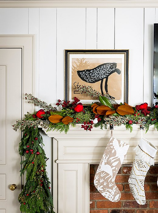 A red cardinal perches between red berries and a magnolia branch in this charming woodland vignette.