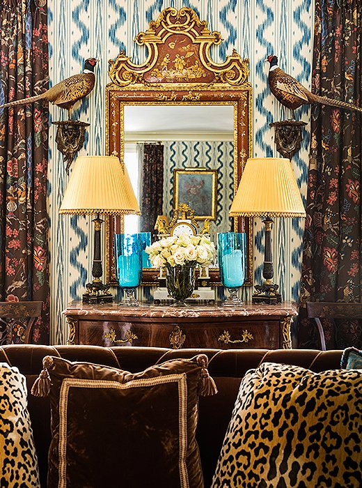 An English chinoiserie mirror was hung above a Louis XV-style commode and flanked with a pair of pheasants. Touches of gold echo the glow of the sofa's brown velvet as it catches the sun.