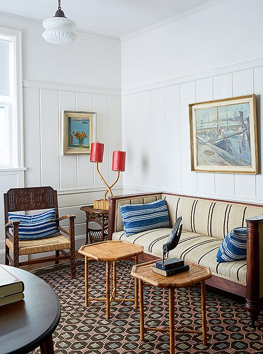 A seating area in one of the suites features an eclectic collection of antiques, including an English sofa, bamboo pieces from the South Pacific, and Nordic paintings.