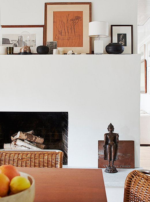 The dining room's fireplace showcases Laura's appreciation for modernist design. Functional and void of ornamentation, its mantel hosts wooden Tibetan vessels and a lamp by Aero Studios. On the hearth, a vintage copper printing plate and a bodhisattva lend a sense of calm.