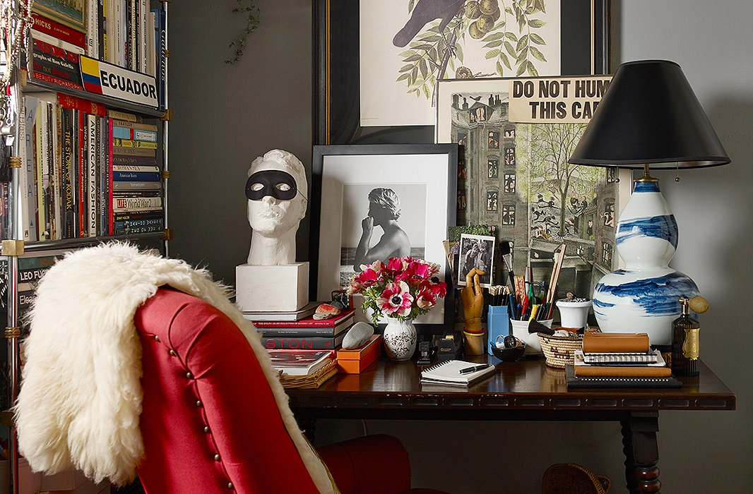 "Michael Bastian's ""home office"" centers on a spindle-leg table flanked by a masked bust and a Bunny Williams Home lamp. The black-and-white photograph of a lifeguard, a work by photographer Matt Albiani, leans against a wall painted in Glidden's Ascot Blue."