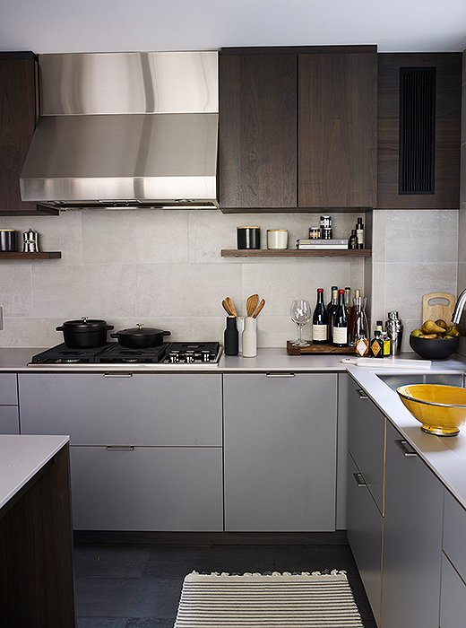The couple kept things streamlined in the kitchen with the help of the design firm Henrybuilt. Upper cabinets in dark wood lend warmth to the otherwise gray palette.