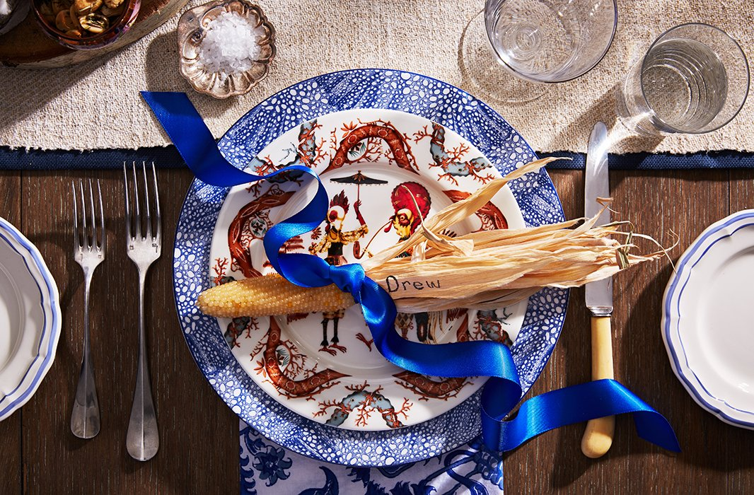 For the place settings, a touch of blue mixed in with rich red and golden hues creates a fresh take on an autumnal palette.