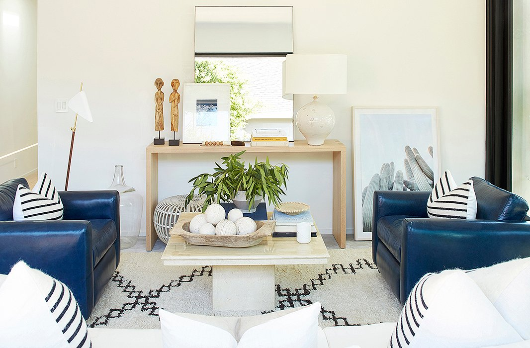 Between a midcentury-style floor lamp by AERIN and a cacti print casually leaned against the wall sits a console arranged with a ceramic lamp, an oversize mirror, and a white rattan Albini ottoman.