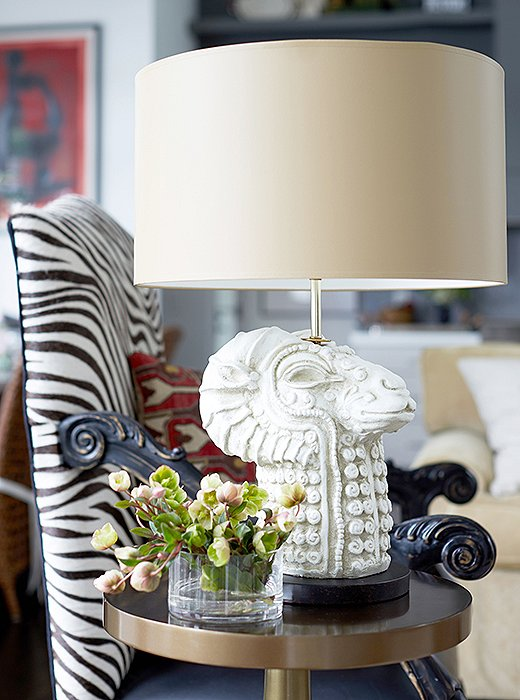 """This is my little ethnic moment,"" Barbara says of the pairing of an African chair and her own artful Mythic Llama lamp. She bought the chair from a vendor who was exhibiting across the aisle from her at one of the many trade shows she's participated in since founding her business in 1997."