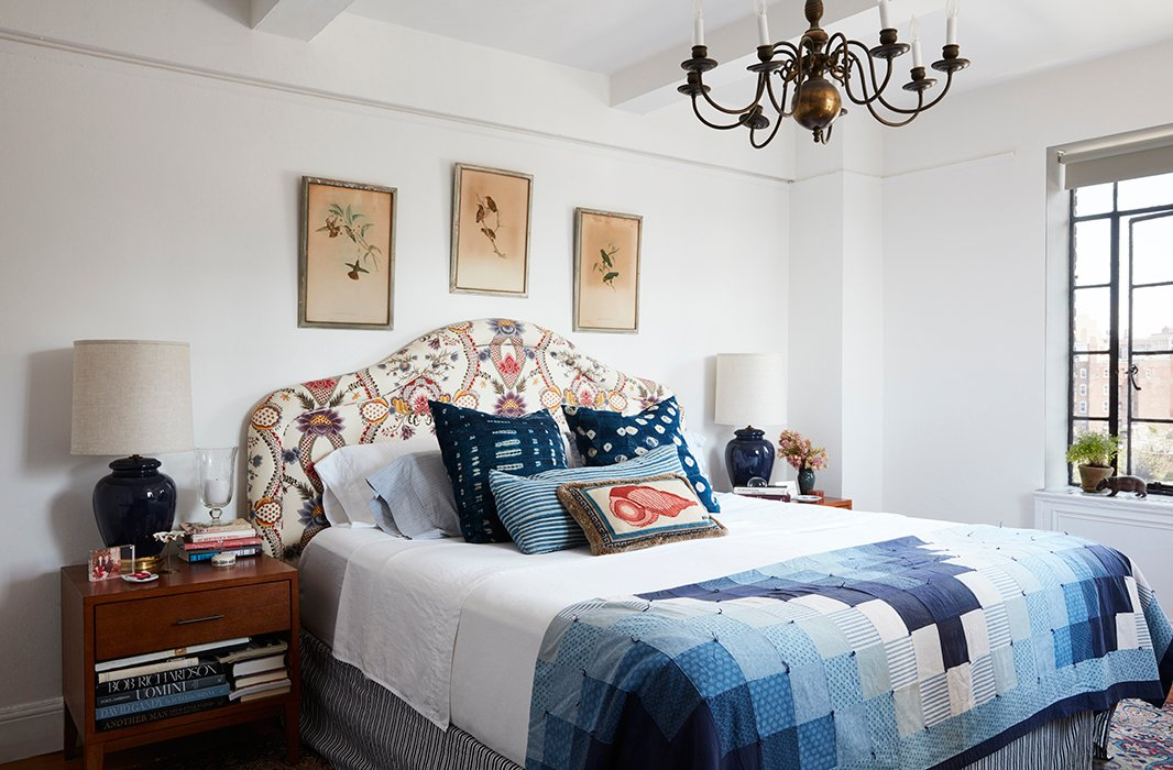 In the bedroom, a trio of Audubon prints crowns an upholstered headboard. Indigo pillows and a patchwork throw offer as much comfort as the tarnished chandelier does tradition.