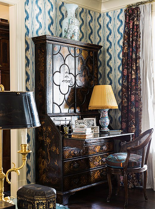 "A secretary desk embellished with chinoiserie motifs hosts a lamp that was once a vase. Silver accents and stacks of books transform this simple ""station"" into a vignette."