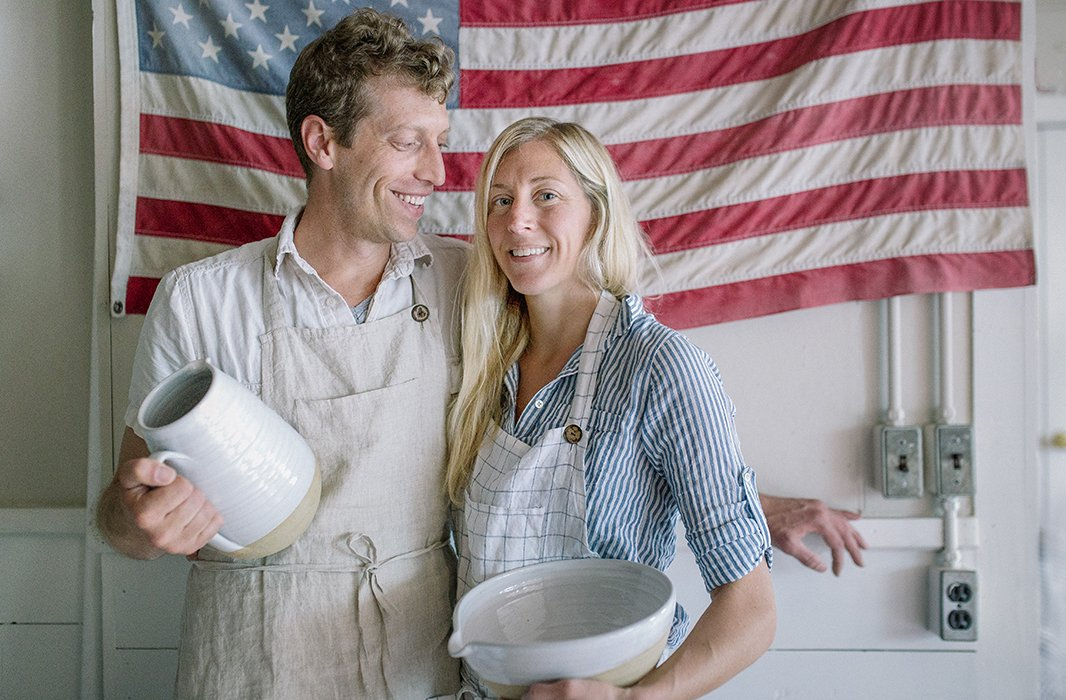 Founders James and Zoe Zilian in Farmhouse Pottery's Woodstock, VT, studio, holding the Farmer's Pitcher and Pantry Mixing Bowl.