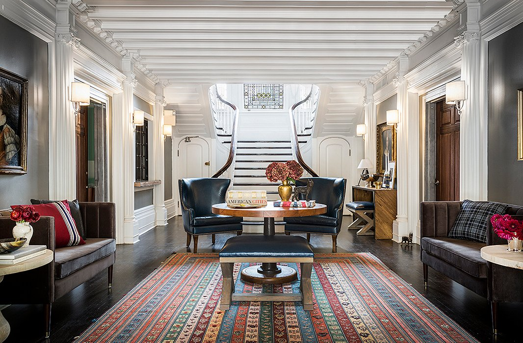 A pedestal table by Noir flanked by a pair of leather wingbacks and a navy leather ottoman by Brownstone Upholstery form a focal point in The George's lobby. A patterned rug adds depth and definition to the expansive space.
