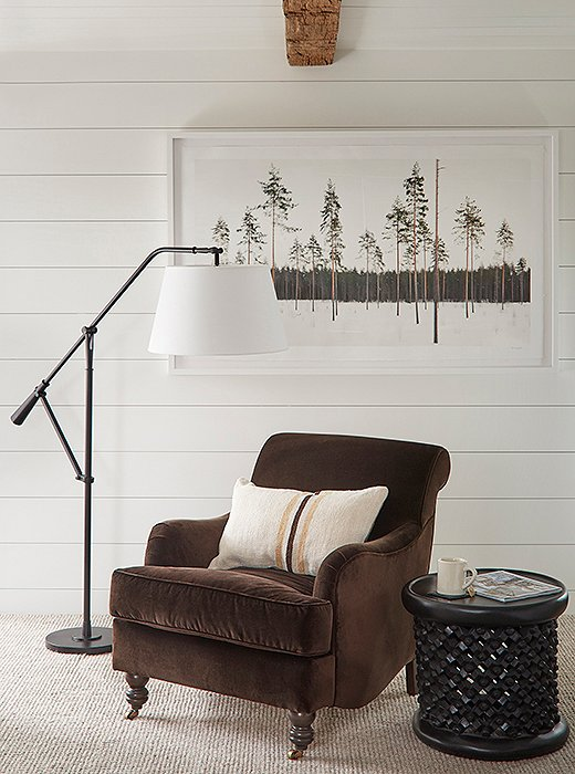 A chair upholstered in rich brown velvet sits next to a floor lamp by Ralph Lauren Home and a carved-wood stool turned side table.