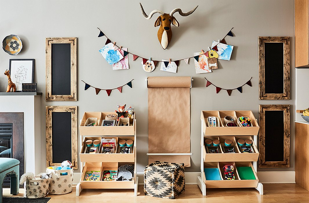 Open bins keep toys organized and within easy reach. Though currently a space for paint and chalk, the areacan be clearedfor a desk down the road.