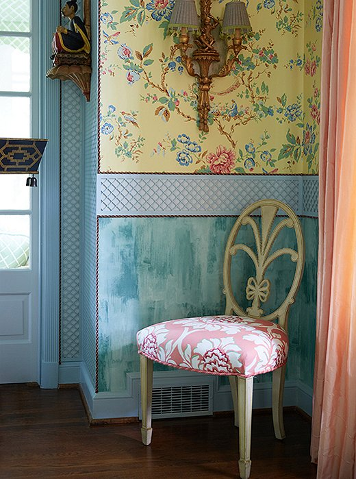 Trimmed wallpaper, a gilded sconce, and silk drapes create grandeur in a far corner.