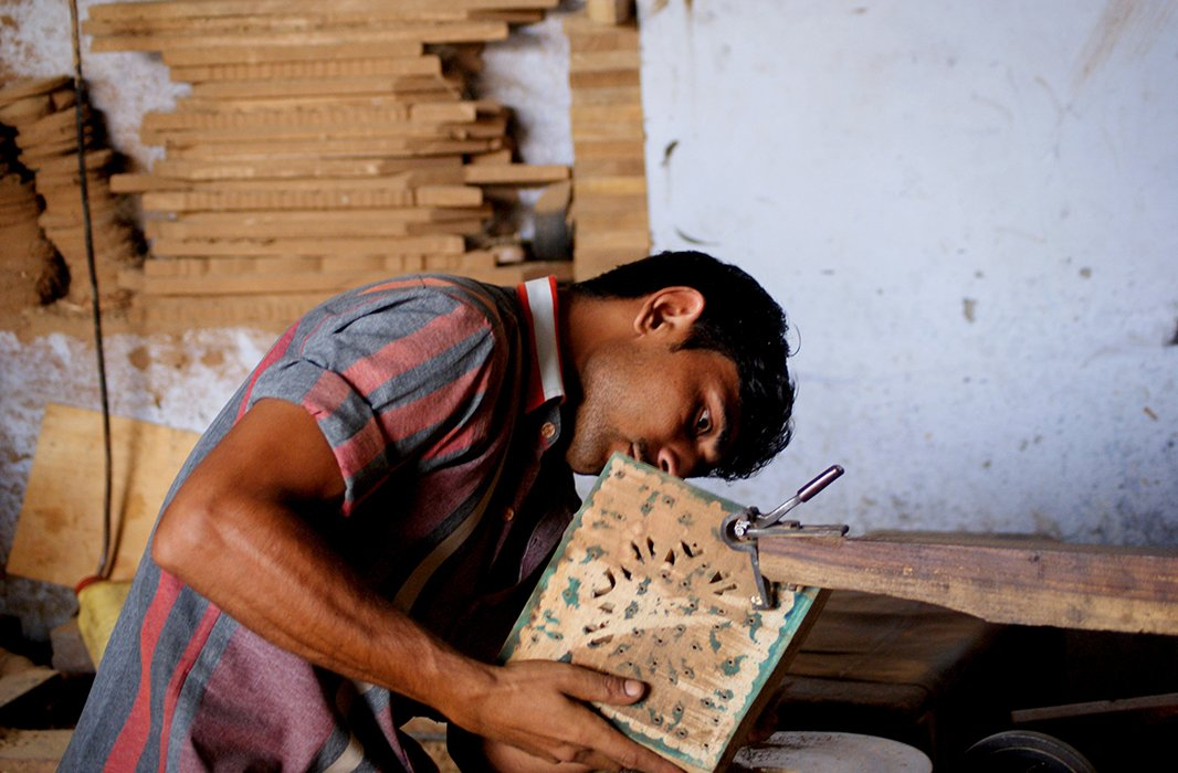A woodworker perfects a delicately carved pattern. Carved wood is frequently combined with brass and other metals to produce a finished piece. Photo courtesy of Mela Artisans.
