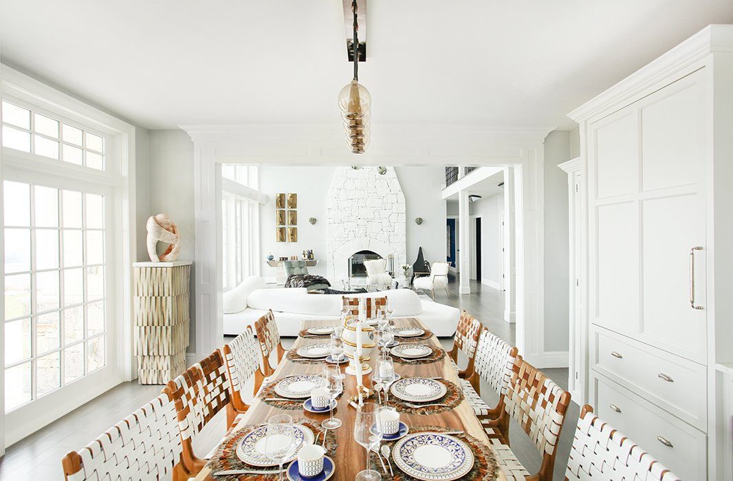 """Set just off an open-plan kitchen, the dining space features a table topped with an Indonesian walnut slab surrounded by chairs in woven leather. To the left, a pedestal constructed of untreated wood hosts a pink marble sculpture. """"The tones of all the pieces reflect those you'd find outside,"""" notes Sasha, """"and add a feeling of warmth to the whole room."""""""