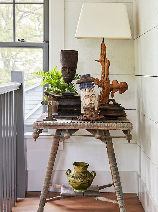 African masks and a lamp crafted from a sculptural piece of driftwood form a well-collected vignette atop a spindle-leg table. T.R. picked up the green ceramic vessel at a souk in Marrakech.